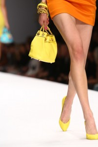 Woman on runway with yellow bucket bag
