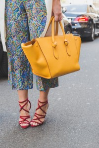 Woman stands outside holding yellow tote bag