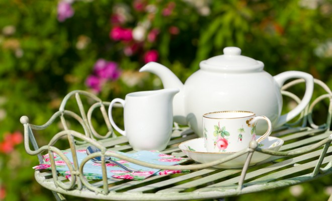 Tea pot and cups outside on a garden table