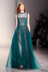 Model walks runway with Victorian-inspired high neckline and embellishment
