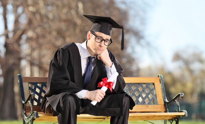 man holding diploma in the park