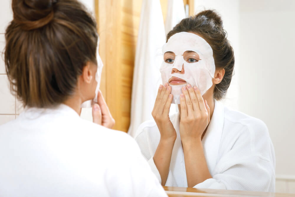woman applying sheet mask