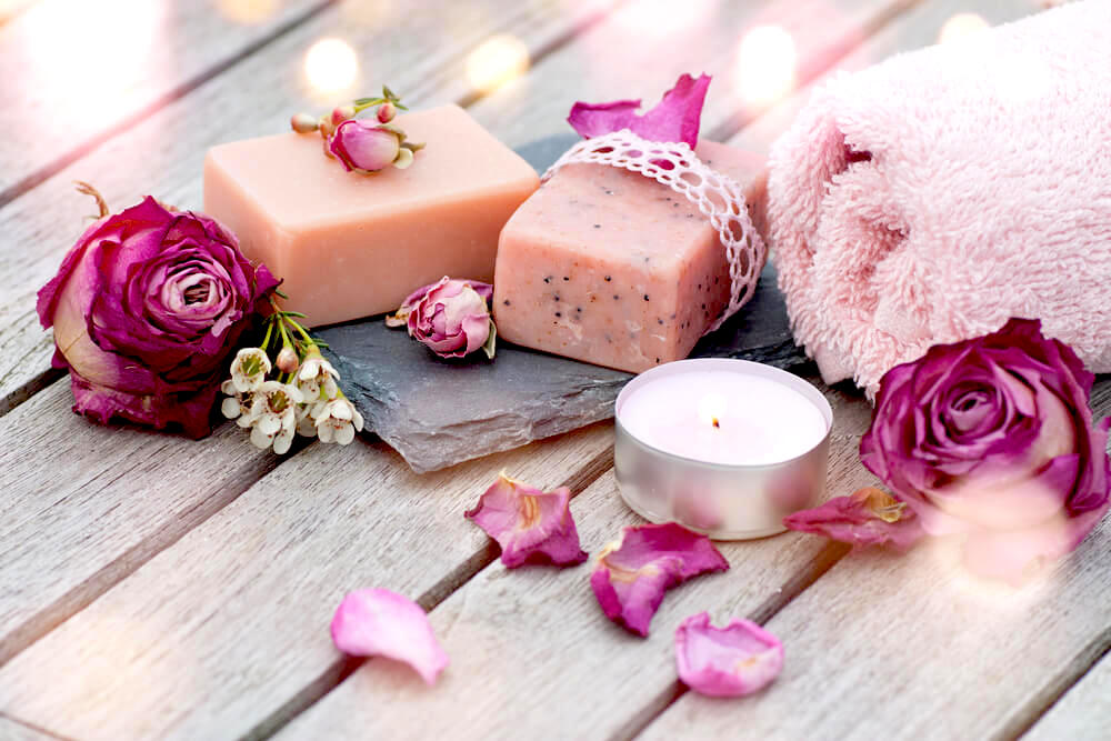 Pink spa soaps and candles on wooden table
