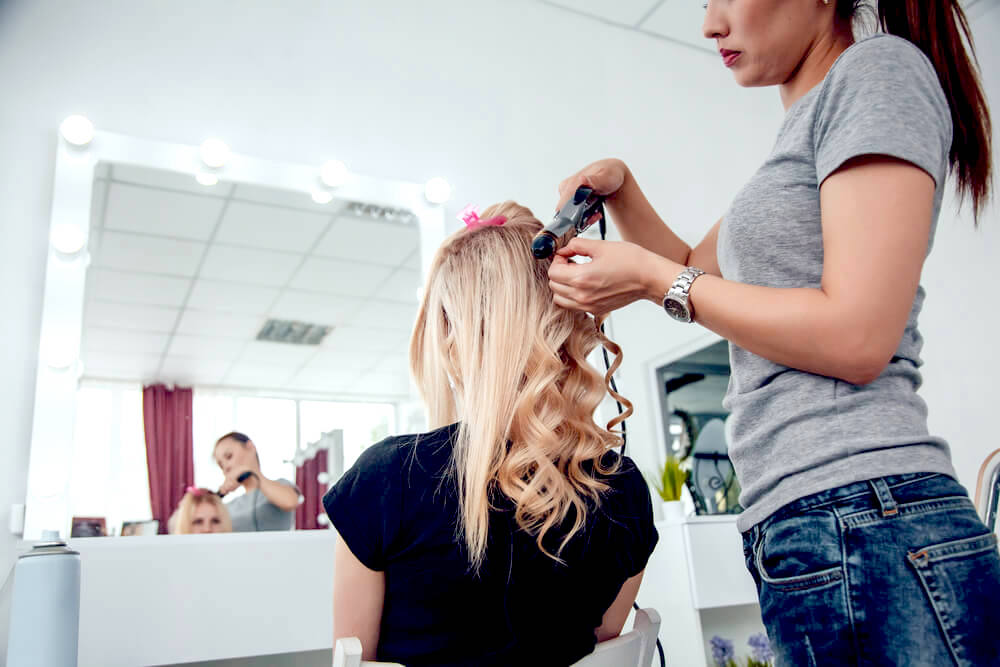 Hairstyling curling woman's blonde hair in hair salon