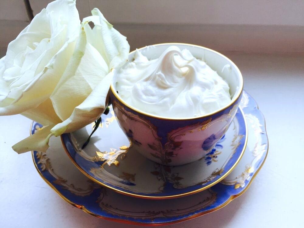 DIY body butter in a bowl with a white rose