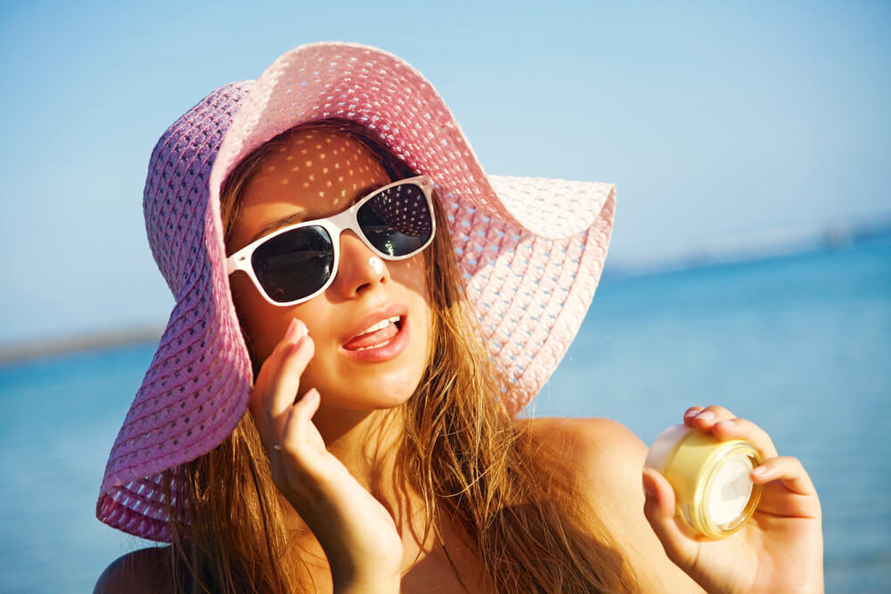Young woman applying moisturiser in the sun, wearing a sunhat