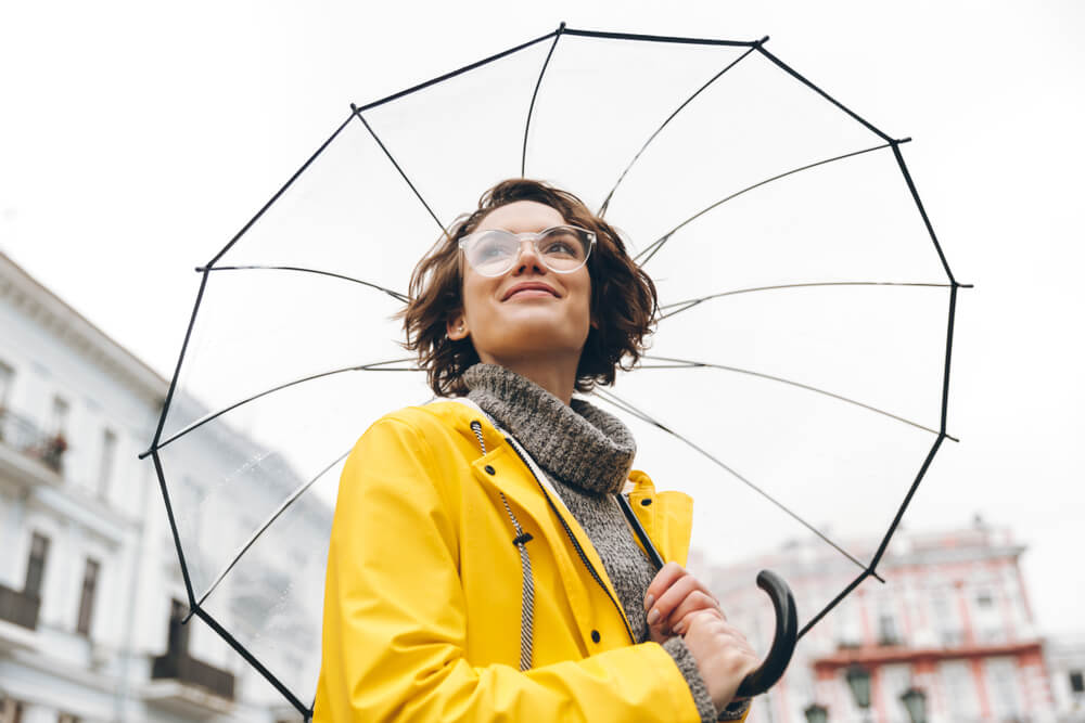 Woman in yellow raincoat holding a transparent umbrella