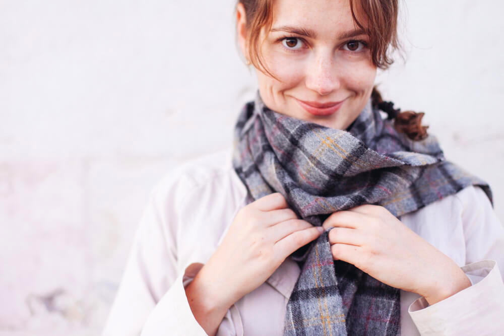 Smiling woman adjusting her grey scarf