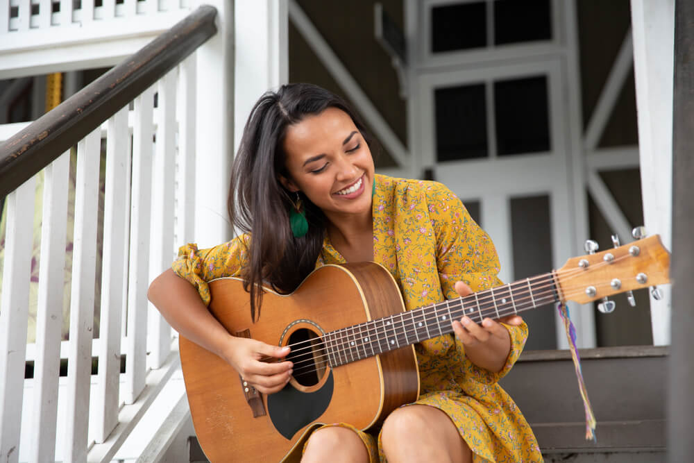 Woman playing guitar on the porch