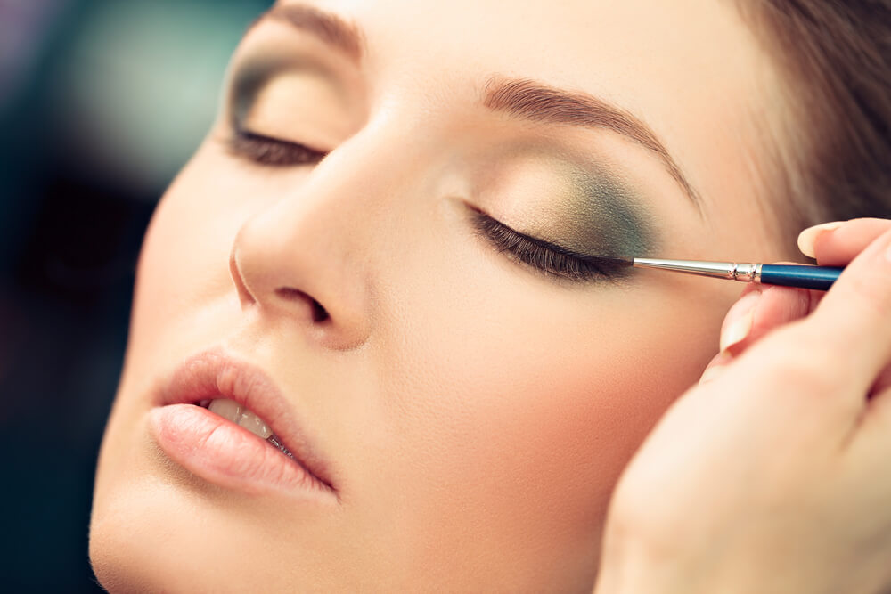 Applying teal eyeshadow