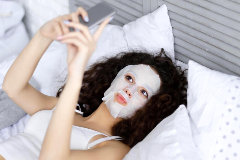 Woman with sheet mask, taking a selfie in bed
