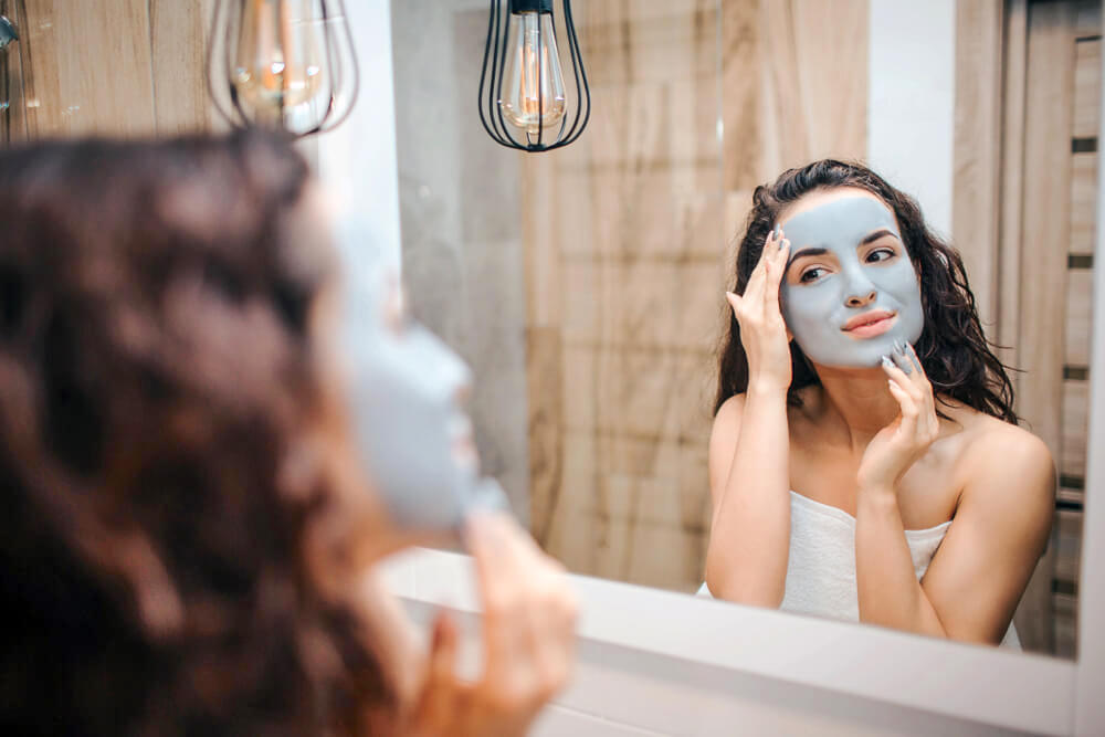 Woman applying clay mask on skin