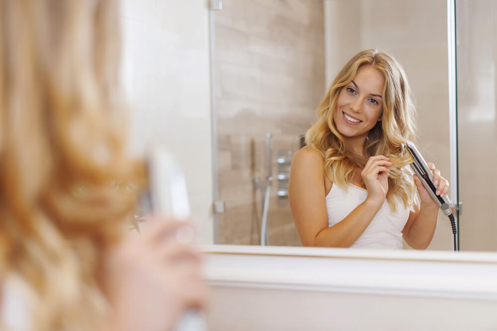 Blonde woman curling hair in front of mirror