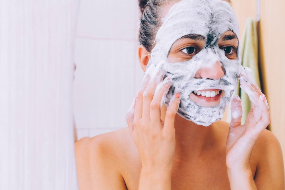 Woman applying foaming face mask