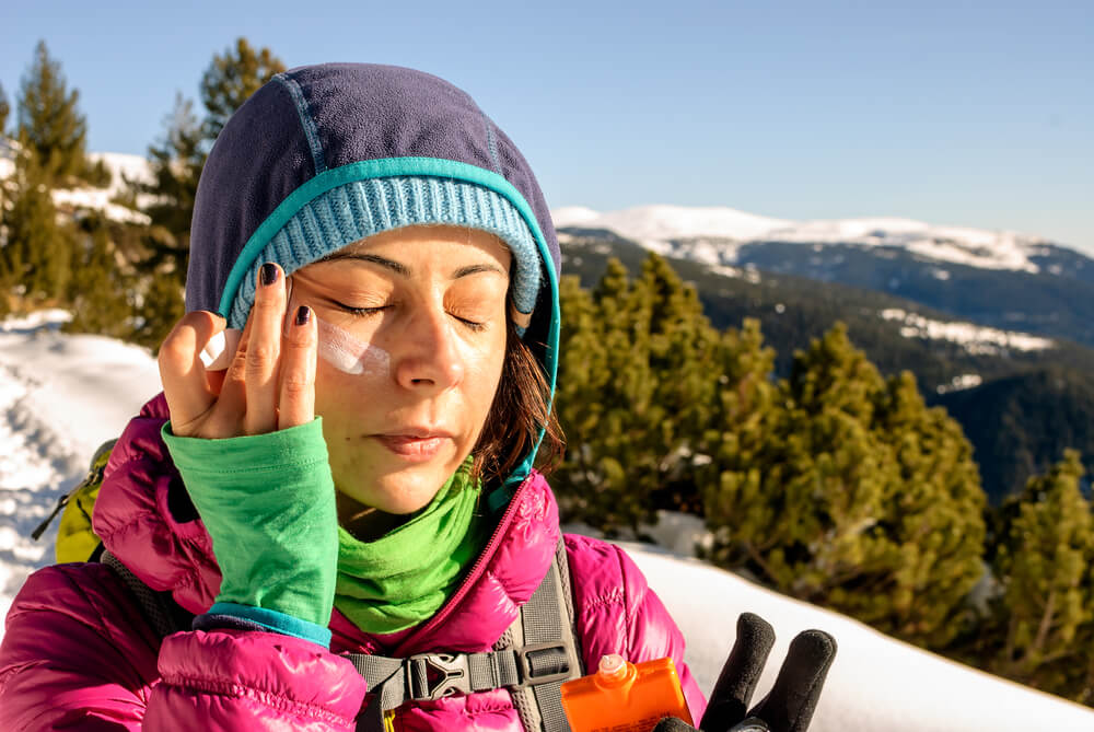 Skiing woman applying sunscreen