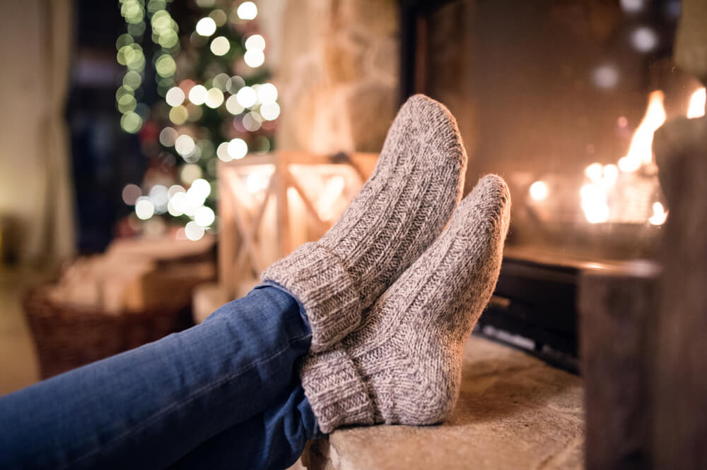 Woman wearing socks with feet up next to candles