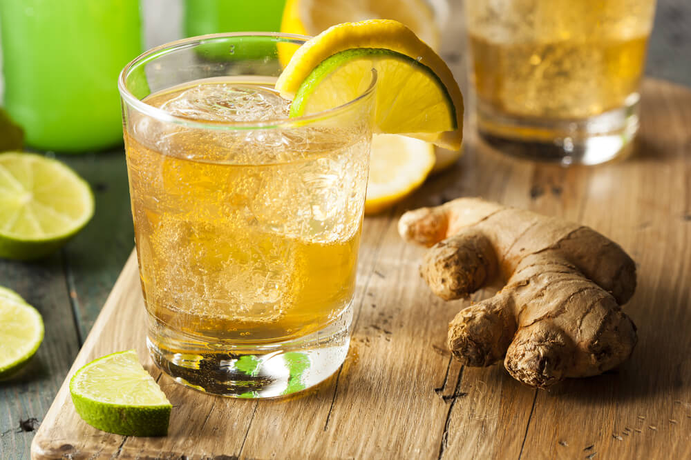 Glass of ginger beer with ginger root next to it