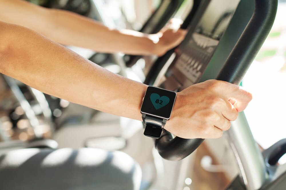 Hands on treadmill with fitness watch