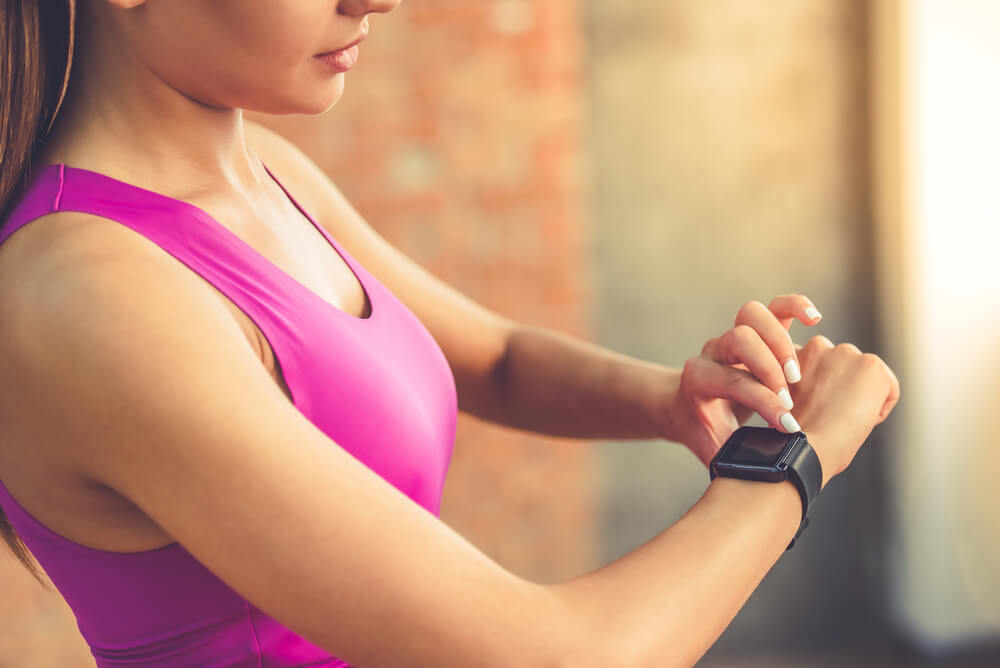 Woman touching fitness watch on wrist