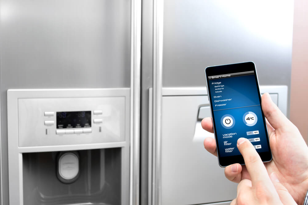 Man using phone with smart fridge