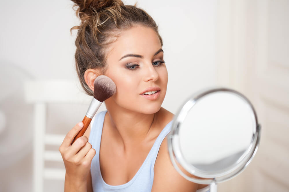 Woman using makeup brush on face