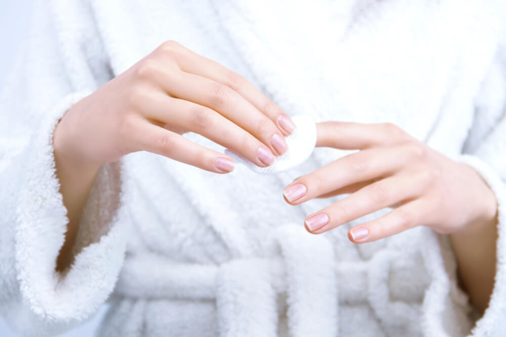Woman wiping nails with cotton pad