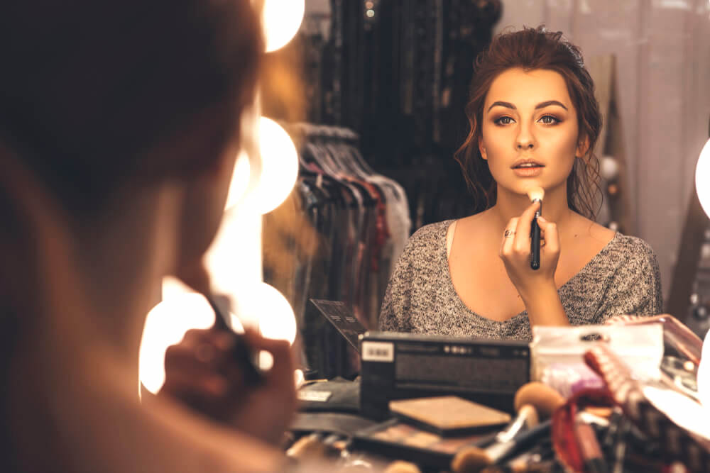 Young woman applying makeup in the mirror