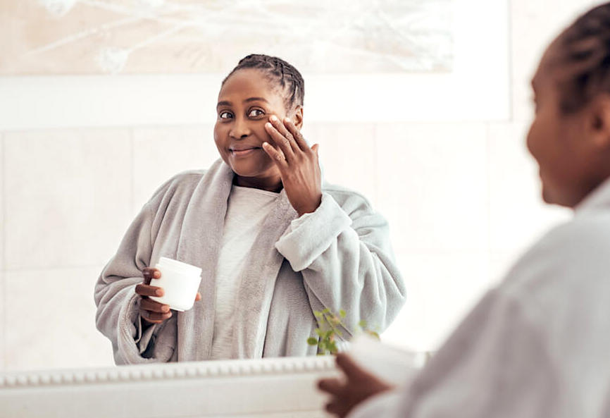 Woman applying face moisturiser in front of bathroom mirror
