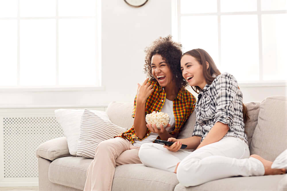 Two female friends enjoying watching film at home