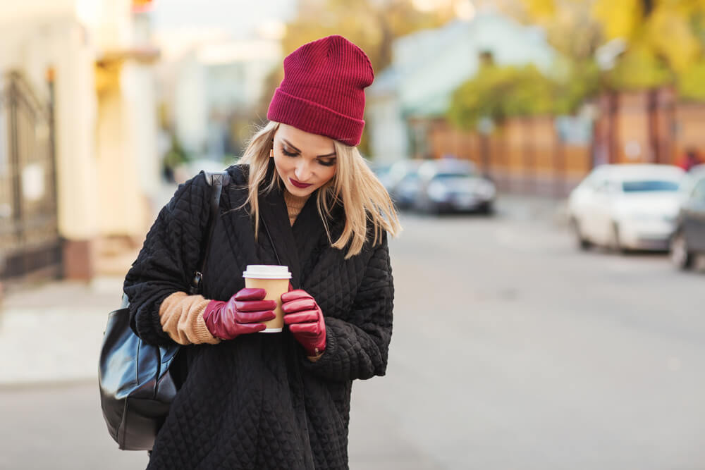 Woman in coat and beanie holding a takeaway cup of coffee