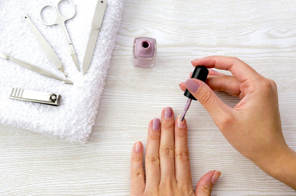 Applying nail polish, surrounded by nail care
