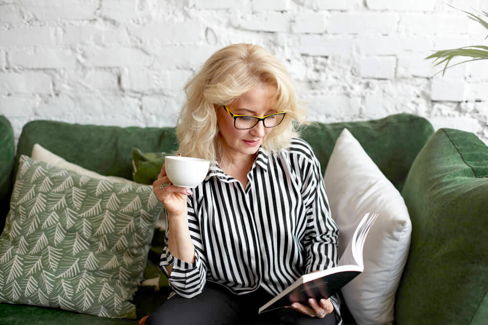 Woman with glasses reading on the couch, holding a cup of coffee