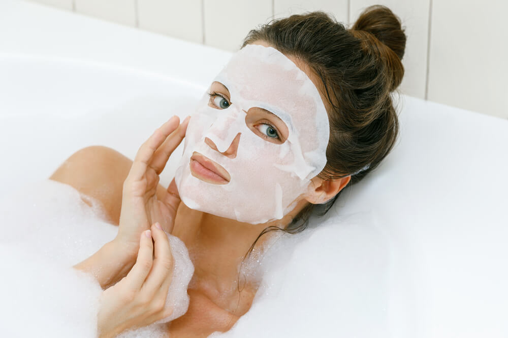 Woman with sheet face mask in bath