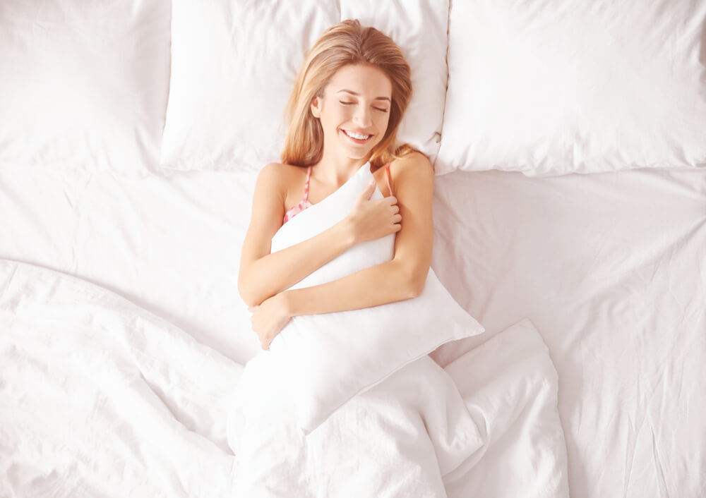 Happy woman in bed hugging pillow